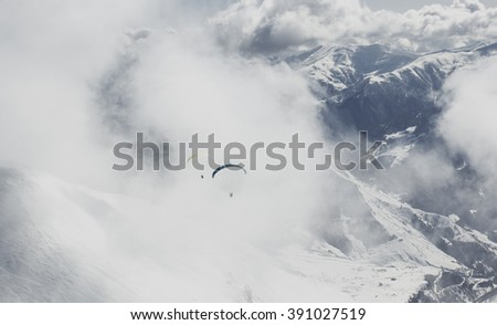 Flying on paraglider in the sky over the Caucasian mountains. Landscape - stock photo