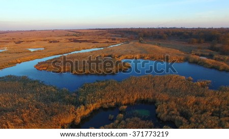 Flying Over The Lake With Reeds at Sunset in Autumn - stock photo