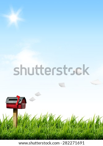 flying paper letter and post box on green grass lawn field over blue sky white clouds sunlight beaming sky background - stock photo