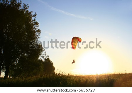 Flying parachutist in front of sun - stock photo