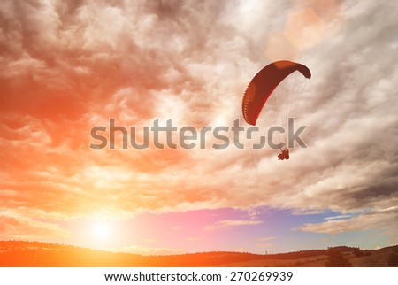 Flying paraglide over the valley in a sky with stormy clouds at light of sunset - stock photo