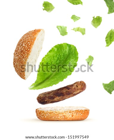 Flying parts of hamburger isolated on white - stock photo