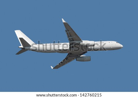 Flying passenger aircraft, isolated on a blue background - stock photo