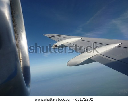 Flying plane wing and motor in a deep blue sky - stock photo