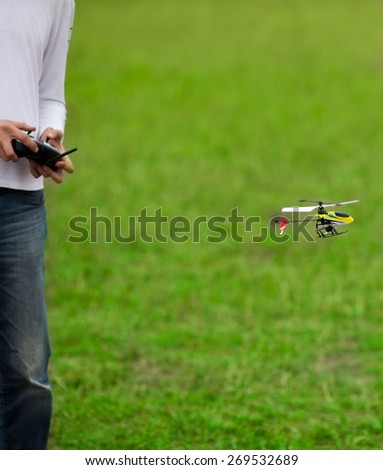 Flying RC model and hands holding transmitter - stock photo