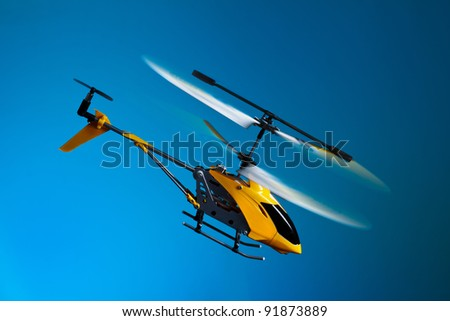 Flying remote controlled helicopter - stock photo