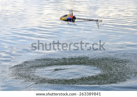 Flying remote controlled helicopter in motion over the water - stock photo