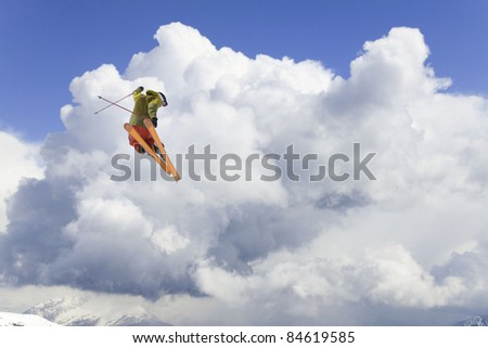 flying skier on mountains, in cloudy sky - stock photo