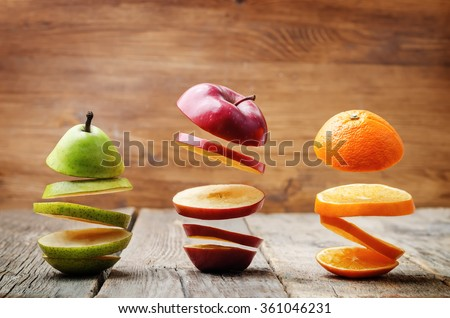 flying slices of fruit: apple, pear, orange on a dark wood background. toning. selective Focus - stock photo