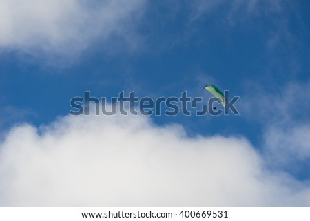 Flying the glider in soft clouds against the blue sky - stock photo