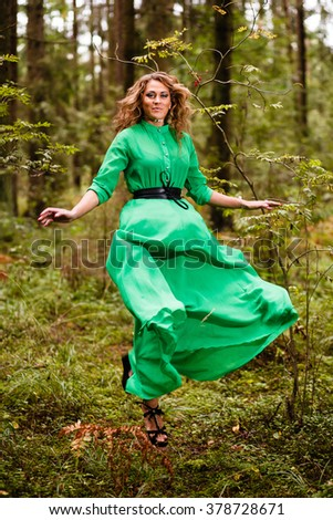 Flying woman in long dress at forest. - stock photo