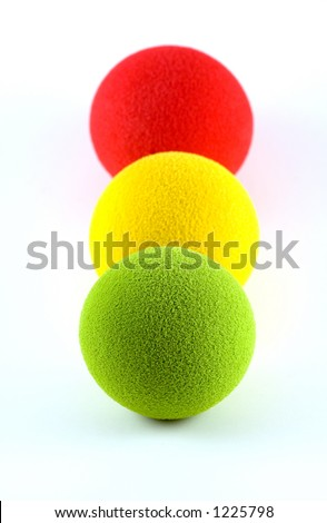 Foam balls lined up in a traffic light metaphor - stock photo