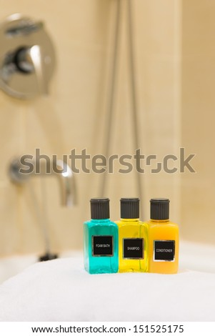 Foam bath, shampoo and conditioner in hotel bathroom - stock photo