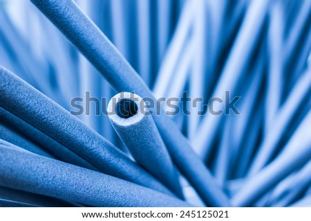 Foam tubes in the warehouse. In blue tones - stock photo