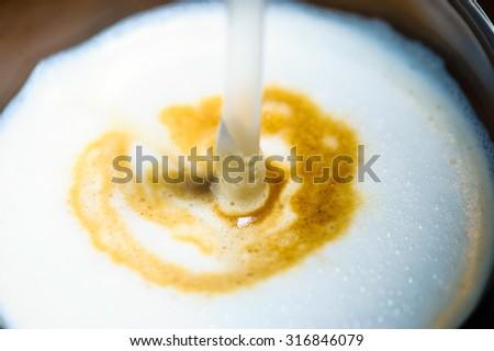 foaming milk in coffee - stock photo