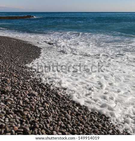 Foaming surface of the sea and the pebble coast - stock photo