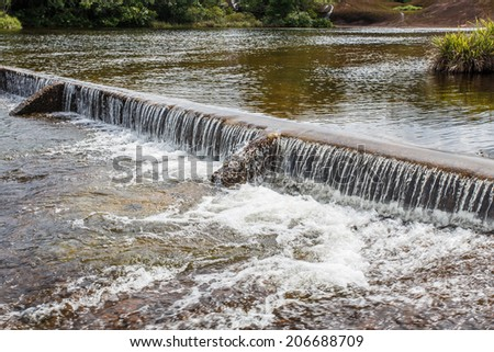 Foaming water coming over a small waterfall from a dam. - stock photo
