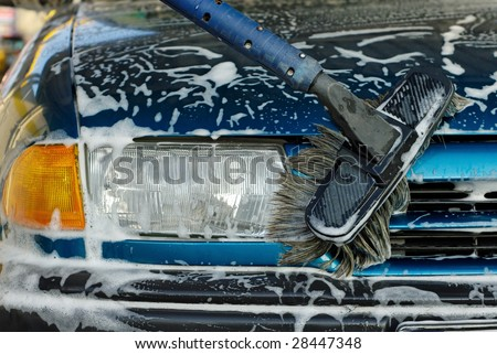 Foamy front of a blue car being cleaned - stock photo
