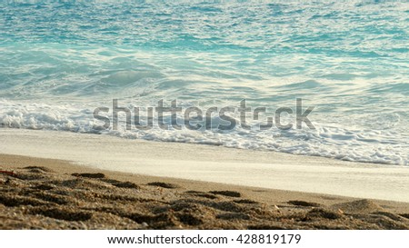 Foamy surfs of a turquoise sea on a sandy beach at sunset.