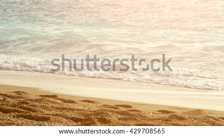 Foamy surfs of a turquoise sea on a sandy beach at sunset. Warm colors. - stock photo