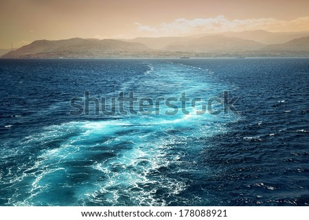 Foamy track behind the stern of the ship overlooking the coast - stock photo