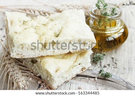 Focaccia italian bread slices with olive oil and ears of wheat placed over wooden table - stock photo