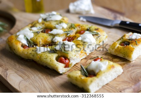 Focaccia with cherry tomatoes, basil pesto and goats cheese - stock photo