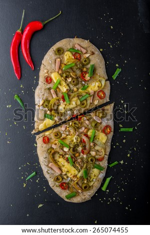 Focaccia with olives, peppers and chicken on a black board - stock photo