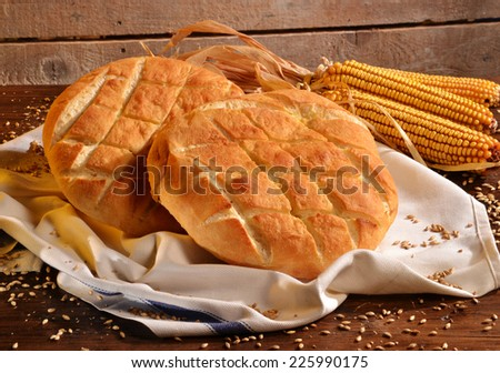 Foccacia Italian bread on rustic wood table and ingredients.Rustic bread and corn on an old vintage wood table. - stock photo