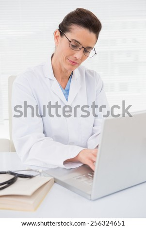 Focus doctor using laptop in medical office