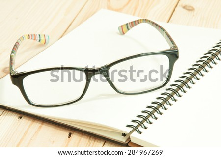 focus eyeglasses on a notebook on the wooden table , pair of glasses