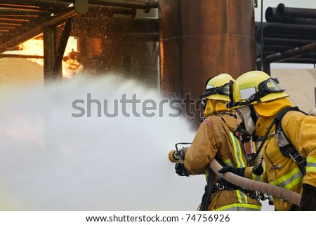 Focus is on the firefighter in the front holding the nozzle. - stock photo
