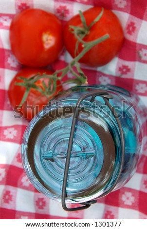 Focus is on the jar lid.  Blue glass jar with a wire holding the lid onto it, used for canning fruits and vegetables, sitting on a vintage table cloth. - stock photo