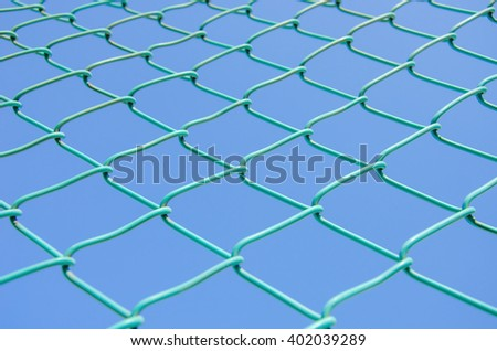 Focus of green wired fence with blue sky backgrounds.