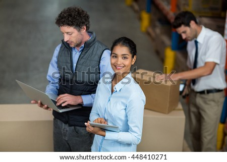 Focus of happy manager is smiling and looking the camera during work in a warehouse