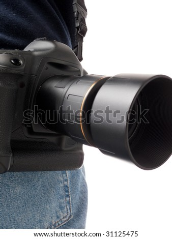 Focus on a digital SLR camera with lens and hood connected, hanging off the back, with the back pocket of denim jeans visible, isolated on white.