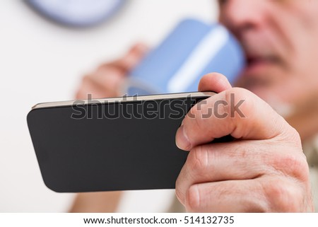 focus on a generic mobile phone held by a mature man blurred on the background in his kitchen