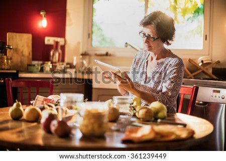 Focus on a middle aged woman looking at recipes on a tablet in a luminous red kitchen. She is sitting at a wooden table with fruits, old fashioned jar and utensils around her. Blur background - stock photo