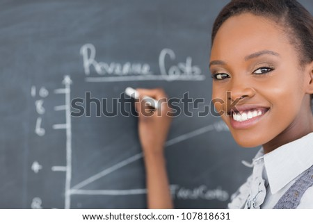 Focus on a teacher drawing a chart on a blackboard in a classroom - stock photo
