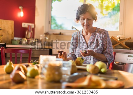 Focus on a woman holding pomegranates in a luminous kitchen sitting at a wooden table with pears and utensils around her, to make rustic and old fashioned jar of fruits Blur background Shot with flare - stock photo