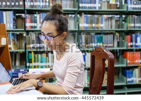 focus on Asian student concentrating on study in library with stress. young adult woman wear glass sit in front of laptop computer alone.