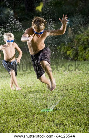 Focus on boy, 9 years, jumping through water spray from lawn sprinkler - stock photo