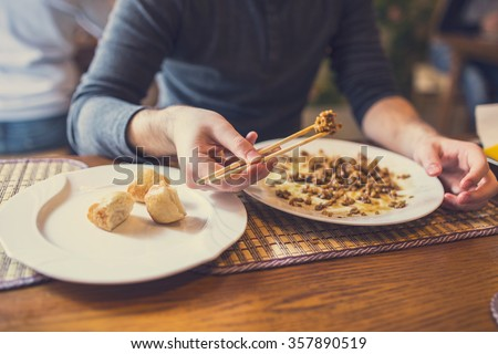 Focus on bread while in background man in eating chinese food with chopsticks - stock photo
