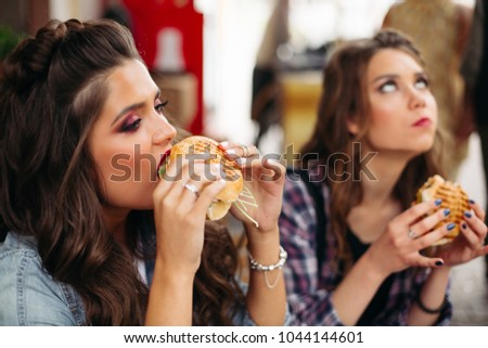 Focus on brunette girl with bright make up enjoying delicious burger against unfocused girlfriend rolling up her eyes in delight, holding burger in hands.