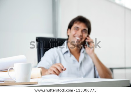 Focus on coffee cup with male architect answering phone call in background - stock photo