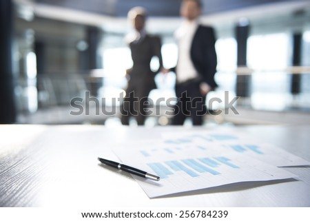 Focus on documents and pen on the table. Blurred people on background. - stock photo