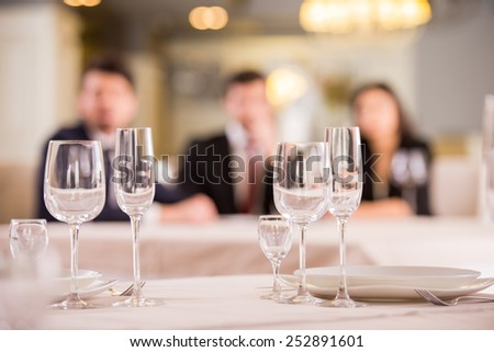 Focus on empty glasses. Three business partners are meeting in restaurant on background.