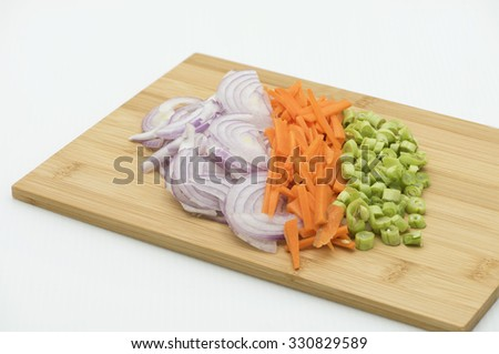 Focus on foreground onions, carrots and green beans. Blurring towards the background. Basic vegetable for cooking. Chopped, sliced and cut vegetable, a preparation of ingredients for cooking. - stock photo