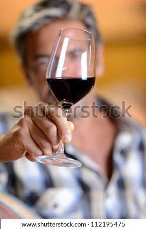 Focus on glass of red wine hold by winemaker - stock photo