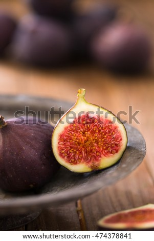 Focus on half sliced and one whole fig. Group of figs at the background out of focus.